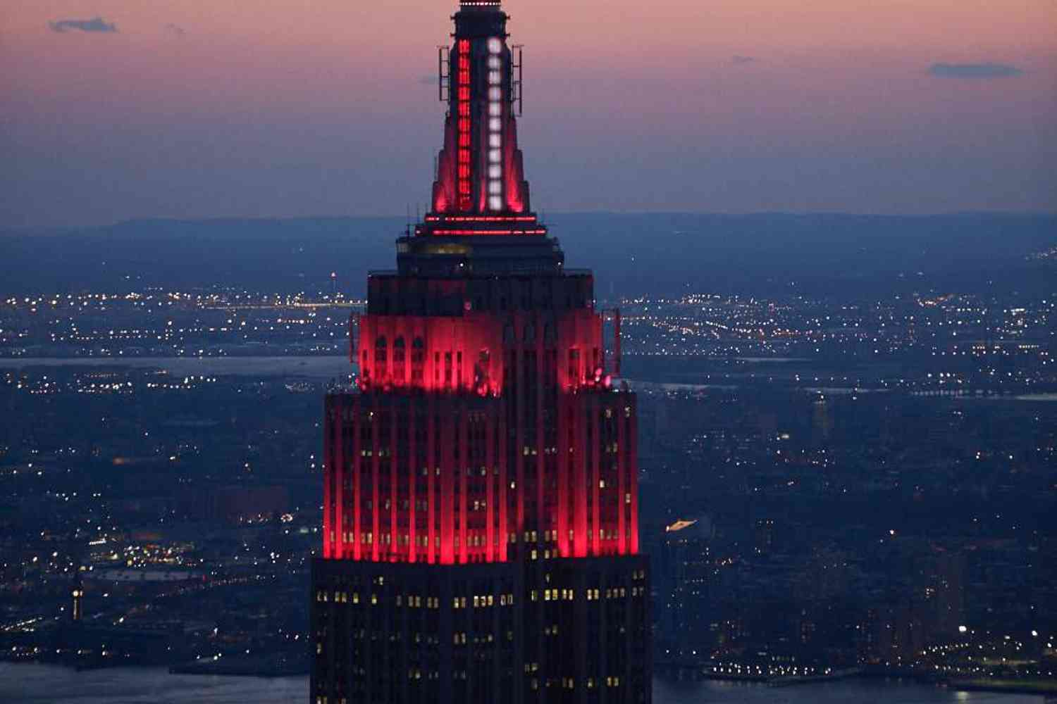 Empire State Building lit up with red, flashing light to honor healthcare workers